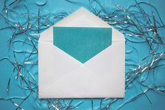 Christmas composition. Envelope with a card. tinsel decorations on blue background. Copy space royalty free stock photo