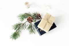 Christmas composition. Festive wrapped Christmas gift boxes with pine branch with cones and silk ribbon on white table. Background, winter design. Flat lay, top stock photo