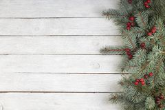 Christmas composition of fir branches and berries of viburnum on a white wooden background. Top view with copy space. stock photography