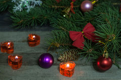Christmas composition of fir branches decorated bows and balls with burning candles on a wooden background Royalty Free Stock Images
