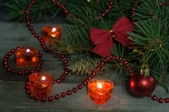 Christmas composition of fir branches decorated bows and balls with burning candles on a wooden background Royalty Free Stock Image