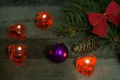 Christmas composition of fir branches decorated bows and balls with burning candles on a wooden background Royalty Free Stock Photos