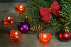 Christmas composition of fir branches decorated bows and balls with burning candles on a wooden background Royalty Free Stock Photo