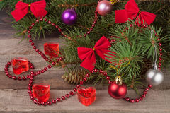 Christmas composition of fir branches decorated bows and balls with candles in shape  heart on a wooden background Stock Images
