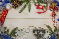 A Christmas composition. Fir branches, tinsel, toys on wooden white background. Flat lay, top view, copy space royalty free stock photography