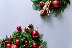 Christmas composition. Christmas fir tree branches, balls, cinnamon sticks and anise stars on gray wooden background. Flat lay. To royalty free stock photography