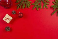 Christmas composition. Fir tree branches, pine cones Christmas decorations and present gift boxes on red background stock images