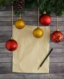 Christmas composition with fir tree, cones, balls, pencil and sheet of writing paper. Wooden plank background. Christmas composition with fir tree, cones, balls Royalty Free Stock Photo