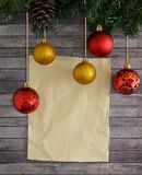 Christmas composition with fir tree, cones, balls and sheet of writing paper. Wooden plank background. Christmas composition with fir tree, cones, balls and Stock Photo