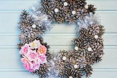 Christmas composition, frame of flowers and cones. A beautiful wreath lies on a light blue background. royalty free stock photo