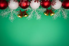 Christmas composition. Christmas gift, bell and ball on green background. Flat lay, top view, copy space stock image