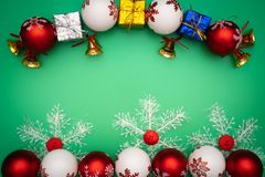 Christmas composition. Christmas gift, bell and ball on green background. Flat lay, top view, copy space royalty free stock image