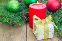 Christmas composition with gift box and candle Stock Photos