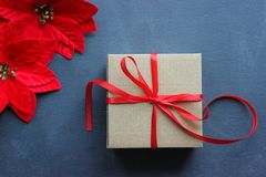 Christmas composition. Gift box with red satin ribbon on a black background. Christmas decor. royalty free stock photo