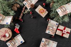Christmas composition with gift boxes, Fir branches, pine cones and money euro on dark holiday background. Xmas and Happy New Year theme. Flat lay, top view royalty free stock photography