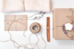 Christmas composition. Gift, dried flowers, cinnamon sticks, knitted scarf, greeting card, kraft envelope, paper box. Flat lay, to. P view stock images