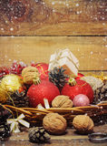 Christmas Composition with Gifts. Basket, red balls, pine cones, snowflakes on Wooden Table. Vintage style Stock Photo