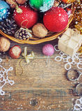 Christmas Composition with Gifts. Basket, red balls, pine cones, snowflakes on Wooden Table. Vintage style Stock Image