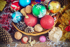 Christmas Composition with Gifts. Basket, red balls, pine cones, snowflakes on Wooden Table. Vintage style Royalty Free Stock Images