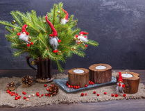 Christmas Composition with Gifts and Burning Candle. Basket, red balls, pine cones, snowflakes on Grey Background Royalty Free Stock Photo
