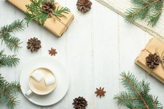 Christmas composition. Christmas gifts, coffee with marshmallows, pine cones, spruce branches on a wooden white background. Flat l stock photography
