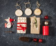 Christmas composition. Christmas gifts, cone, toys on black stone background. Flat lay royalty free stock photo
