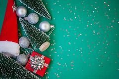 Christmas composition. Christmas gifts, red box, silver balls on green background. Flat lay, top view stock photo