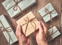 Christmas composition. Christmas gifts in woman hands on wooden background. New year gift decoration on wood board. New Year and C stock image