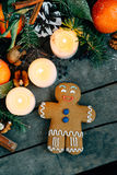 Christmas composition with gingerbread man Tangerines, Pine cones, Walnuts and Candles on Wooden Background, holiday decoration Royalty Free Stock Image