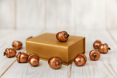 Christmas composition.Golden present box and golden acorns.White wooden table. Mokup with space Stock Photos