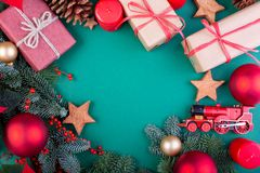 Christmas composition. Christmas green decorations, fir tree branches with toys gift boxes on green background. Flat lay. Top view, copy space stock image