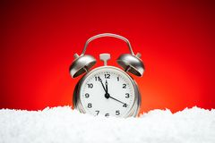 Christmas composition. Greeting card for new year clock Alarm cl. Ock on snow on red background with place for congratulatory text concept countdown to midnight Stock Image