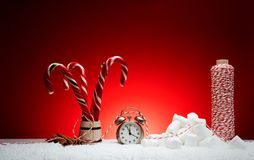 Christmas composition. Greeting card for new year clock alarm cl. Ock toys balls candy stick cinnamon marshmelow thread on snow on red background with place for Royalty Free Stock Images
