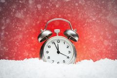 Christmas composition. Greeting card for new year clock Alarm cl. Ock on snow on red background with place for congratulatory text concept countdown to midnight Royalty Free Stock Photography
