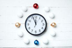 Christmas composition. Greeting card for new year, clock and toy. S balls around on white wooden background Stock Photography