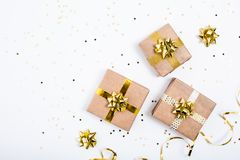 Craft presents decorated with gold bows and serpentine on white background. View from the top. Copy space royalty free stock photography
