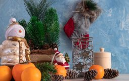 Christmas composition of Christmas objects with a Christmas tree and a snowman. New Year`s decoration. Tangerines with persimmon. stock photos