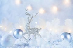 Christmas composition made of Christmas balls and figurine of reindeer on blue winter background. Minimal styled holiday card. Holiday background royalty free stock photography