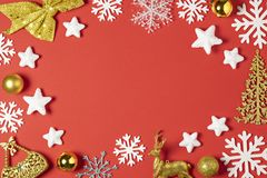 Christmas composition made of white snowflakes, tree, star, ball toy or bauble and deer on red background. New year winter concept stock images