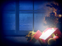 Christmas composition at night with bluish hue dream front view. Christmas composition on Christmas Eve. Glow gift, tree and decoration balls with window Royalty Free Stock Images