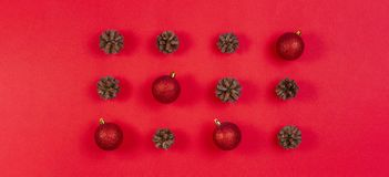 Christmas composition. Pattern made of pine cones and red christmas decoration on red background. Top view, flat lay stock photos
