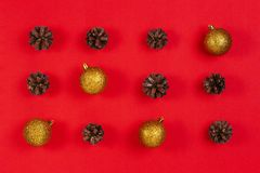 Christmas composition. Pattern made of pine cones, yellow and red christmas decoration on red background stock photo