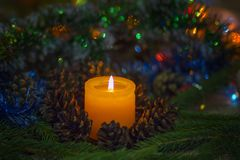 Christmas composition. A burning candle around pine cones and fir branches. Beautiful blurry background with a neat bokeh. It`s al stock photo