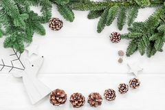 Christmas composition. Pine cones, fir branches on wooden white. Background. Flat lay, top view Royalty Free Stock Photos