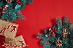 Christmas composition of pine cones, spruce branches and stack of gift boxes on red background Royalty Free Stock Photos
