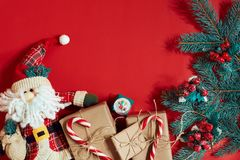 Christmas composition of pine cones, spruce branches and stack of gift boxes on red background Royalty Free Stock Photography
