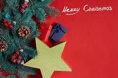 Christmas composition of pine cones, spruce branches and stack of gift boxes on red background Royalty Free Stock Photo
