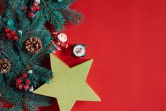 Christmas composition of pine cones, spruce branches and stack of gift boxes on red background Stock Photography