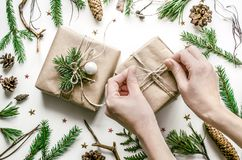 Christmas composition for the preparation for the New Year. The girl`s hands tie a bow on the gift wrapper. royalty free stock image