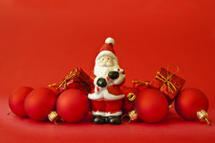Christmas composition - red. Christmas composition with christmas balls, Santa Claus and christmas gifts on red background Royalty Free Stock Photos